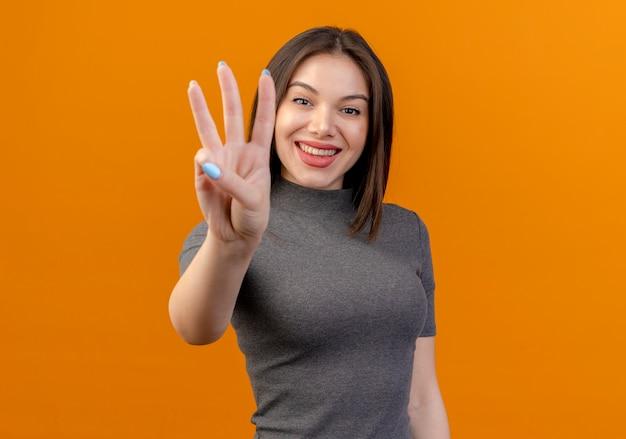 Glimlachende jonge mooie vrouw die drie met hand toont die op oranje achtergrond met exemplaarruimte wordt geïsoleerd