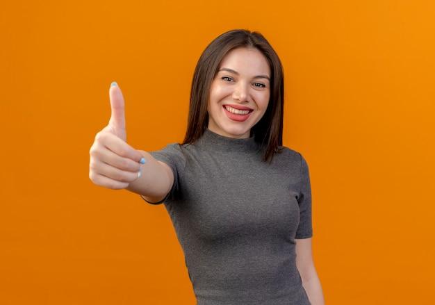 Glimlachende jonge mooie vrouw die duim toont die omhoog op oranje achtergrond met exemplaarruimte wordt geïsoleerd