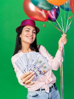 Glimlachende jonge mooie vrouw die een feesthoed draagt die ballonnen vasthoudt en contant geld aan de voorkant op een groene muur steekt