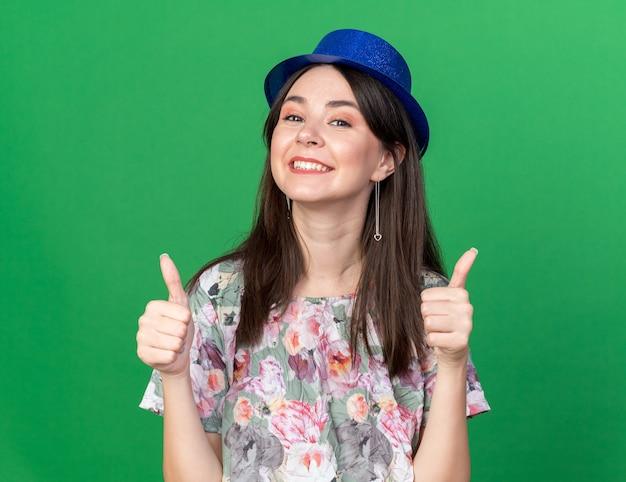Glimlachende jonge mooie vrouw die feestmuts draagt die duimen toont die op groene muur worden geïsoleerd
