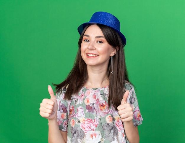 Glimlachende jonge mooie vrouw die feestmuts draagt die duimen toont