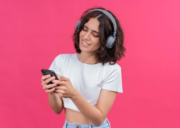 Glimlachende jonge mooie vrouw die hoofdtelefoons draagt en mobiele telefoon op roze muur met exemplaarruimte houdt