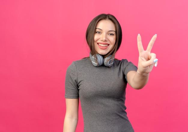 Glimlachende jonge mooie vrouw die hoofdtelefoons op hals draagt die vredesteken doet dat op roze achtergrond met exemplaarruimte wordt geïsoleerd