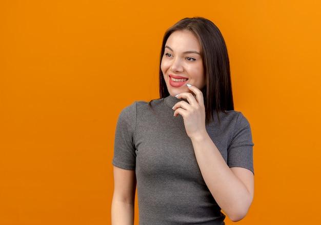 Glimlachende jonge mooie vrouw die kant bekijkt en kin aanraakt die op oranje achtergrond met exemplaarruimte wordt geïsoleerd
