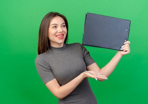 Glimlachende jonge mooie vrouw die kantholding bekijkt en met hand op klembord richt dat op groene achtergrond wordt geïsoleerd