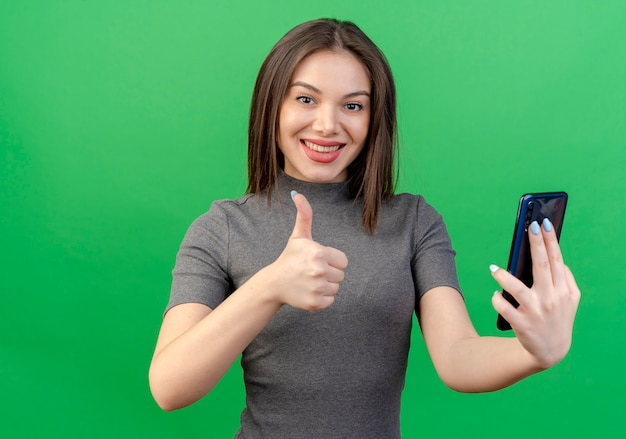 Glimlachende jonge mooie vrouw die mobiele telefoon houdt en duim toont die omhoog op groene achtergrond wordt geïsoleerd