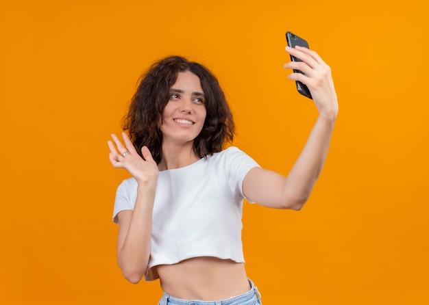 Glimlachende jonge mooie vrouw die mobiele telefoon houdt en ernaar zwaait op geïsoleerde oranje muur met exemplaarruimte