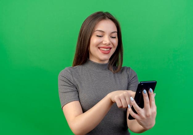 Glimlachende jonge mooie vrouw die mobiele telefoon met behulp van die op groene achtergrond met exemplaarruimte wordt geïsoleerd
