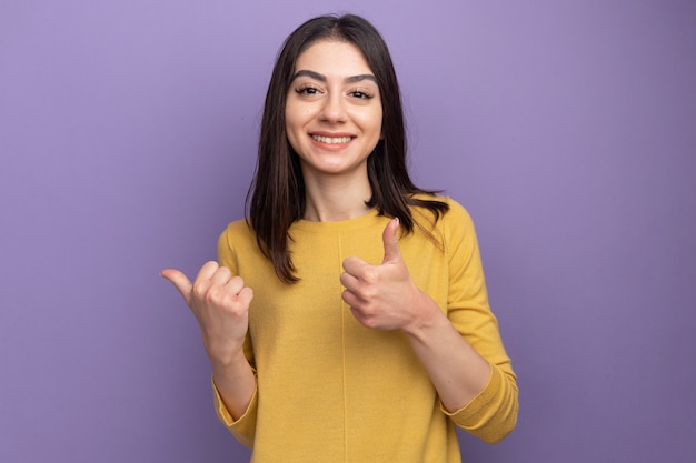 Glimlachende jonge mooie vrouw die naar de voorkant kijkt en naar de zijkant wijst met duim omhoog geïsoleerd op paarse muur met kopieerruimte