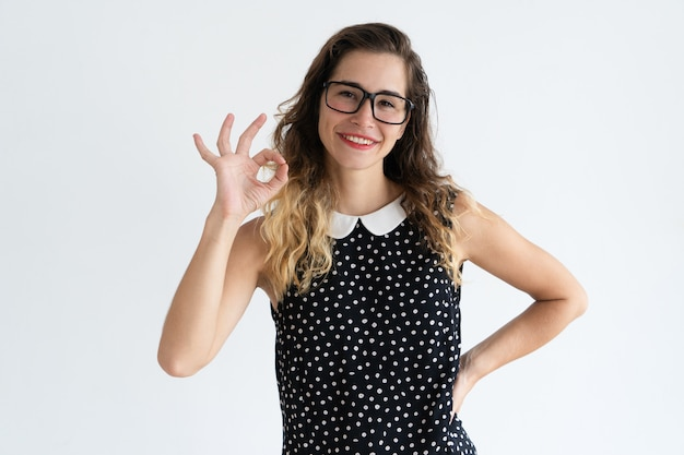 Glimlachende jonge mooie vrouw die ok teken toont en camera bekijkt.