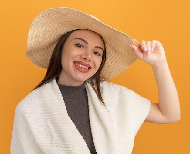 Glimlachende jonge mooie vrouw die strandhoed draagt en grijpt