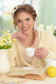 Glimlachende jonge mooie vrouw die thee drinkt met boek in de keuken