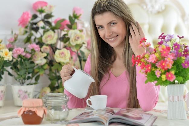 Glimlachende jonge mooie vrouw die thee drinkt met tijdschrift in de keuken