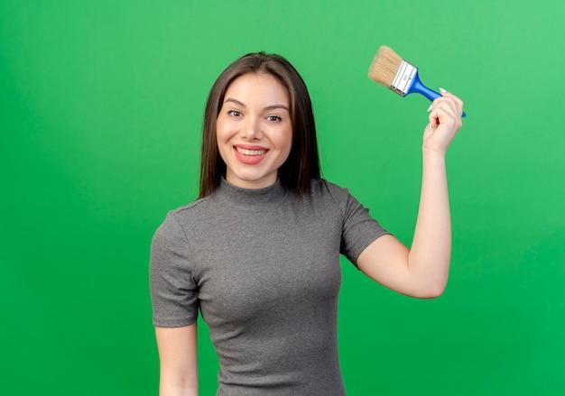Glimlachende jonge mooie vrouw die verfborstel opheft die op groene achtergrond met exemplaarruimte wordt geïsoleerd