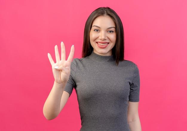 Glimlachende jonge mooie vrouw die vier met hand toont die op roze achtergrond wordt geïsoleerd