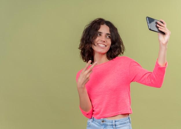 Glimlachende jonge mooie vrouw die vredesteken doet en selfie met mobiele telefoon op geïsoleerde groene muur met exemplaarruimte neemt