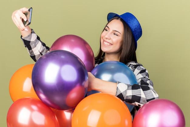 Glimlachende jonge mooie vrouw met blauwe hoed die achter ballonnen staat, neemt een selfie geïsoleerd op olijfgroene muur