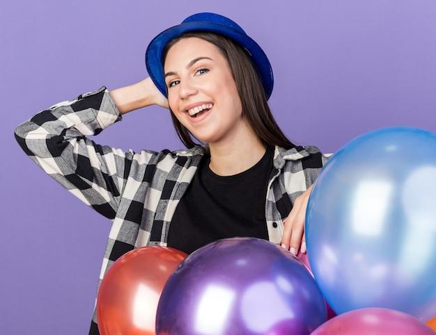 Glimlachende jonge, mooie vrouw met een feesthoed die achter ballonnen staat en hand op het hoofd zet, geïsoleerd op een blauwe muur