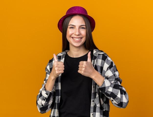 Glimlachende jonge mooie vrouw met feestmuts die duimen laat zien, geïsoleerd op een oranje muur
