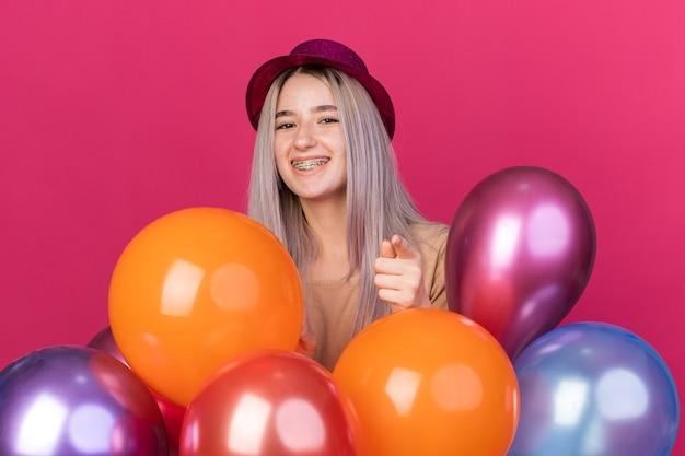 Glimlachende jonge mooie vrouw met feestmuts met beugels die achter ballonnen staan en je een gebaar laten zien dat op een roze muur is geïsoleerd
