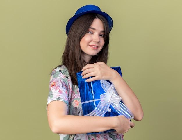 Glimlachende jonge mooie vrouw met feestmuts omhelsde geschenkdoos geïsoleerd op olijfgroene muur