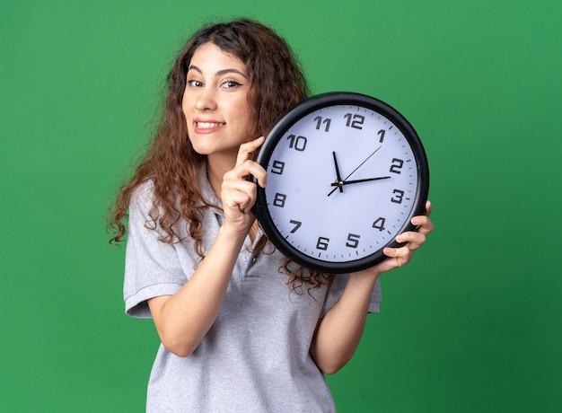 Glimlachende jonge mooie vrouw met klok kijkend naar voorzijde geïsoleerd op groene muur
