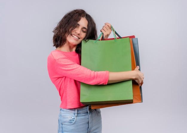 Glimlachende jonge mooie vrouw met papieren zakken op geïsoleerde witte muur