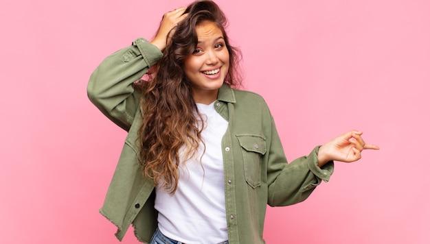 Glimlachende jonge mooie vrouw op roze achtergrond
