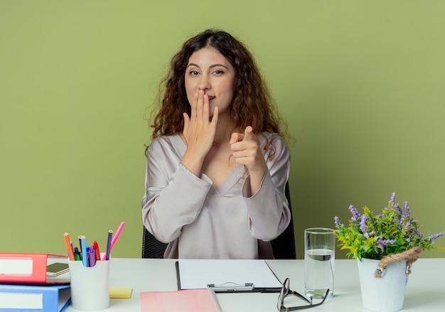 Glimlachende jonge mooie vrouwelijke kantoormedewerker zittend aan een bureau met kantoorhulpmiddelen bedekt mond met hand en toont u gebaar geïsoleerd op olijf achtergrond