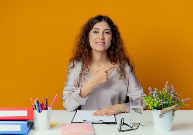 Glimlachende jonge mooie vrouwelijke kantoormedewerker zittend aan een bureau met office tools punten aan kant geïsoleerd op oranje met kopie ruimte