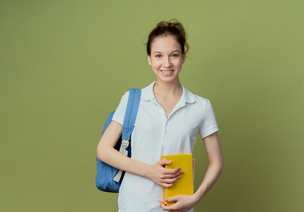 Glimlachende jonge mooie vrouwelijke student die het boek van de achterzakholding draagt die camera bekijkt die op groene achtergrond met exemplaarruimte wordt geïsoleerd