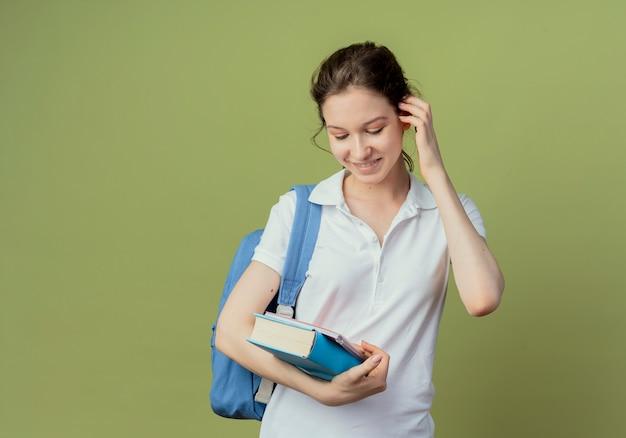 Glimlachende jonge mooie vrouwelijke student die het boek van de achterzakholding en notitieblok draagt die met hand op oor neerkijkt die op olijfgroene achtergrond met exemplaarruimte wordt geïsoleerd