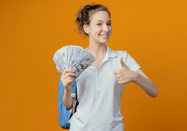 Glimlachende jonge mooie vrouwelijke student die het geld van de achterzakholding draagt en duim toont die omhoog op oranje achtergrond met exemplaarruimte wordt geïsoleerd