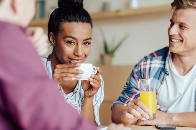 Glimlachende jonge multi-etnische vrienden die koffie en sap drinken in café
