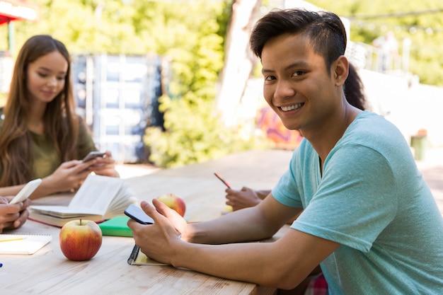 Glimlachende jonge multi-etnische vriendenstudenten die mobiele telefoons met behulp van