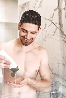 Glimlachende jonge naakte mens die een douche heeft