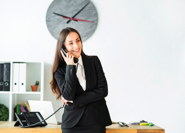 Glimlachende jonge onderneemster bezig in het spreken op telefoon in het bureau