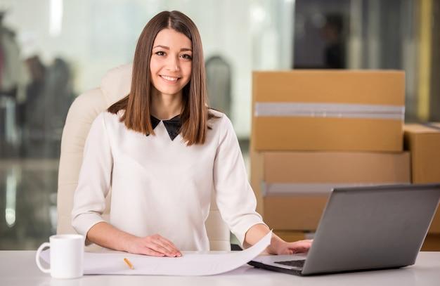 Glimlachende jonge onderneemster die in bureau dichtbij dozen werkt.