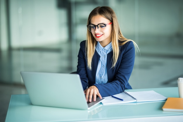Glimlachende jonge onderneemster die op laptop in het bureau typt
