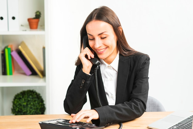 Glimlachende jonge onderneemster die op telefoon in het bureau spreekt