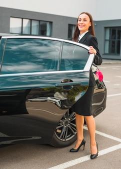 Glimlachende jonge onderneemster die zich met haar zwarte auto bevindt
