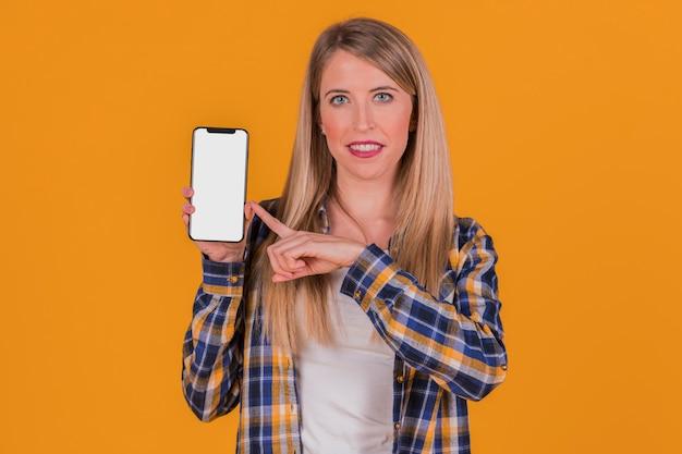 Glimlachende jonge onderneemster die zijn vinger richt op mobiele telefoon tegen een oranje achtergrond
