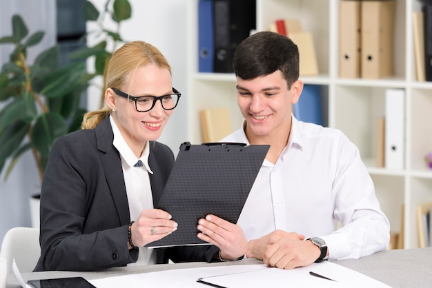 Glimlachende jonge onderneemster en zakenman die digitale tablet in het bureau bekijken