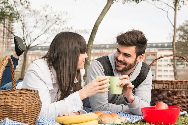 Glimlachende jonge paar roosterende glazen met vers voedsel bij picknick