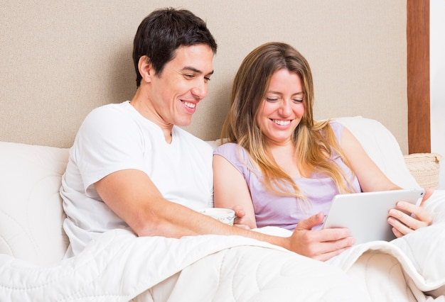 Glimlachende jonge paarzitting op bed die digitale tablet bekijken