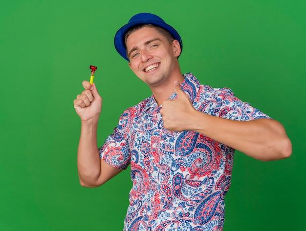 Glimlachende jonge partijkerel die blauwe de partijventilator van de hoedholding draagt ?? die duim toont die omhoog op groen wordt geïsoleerd