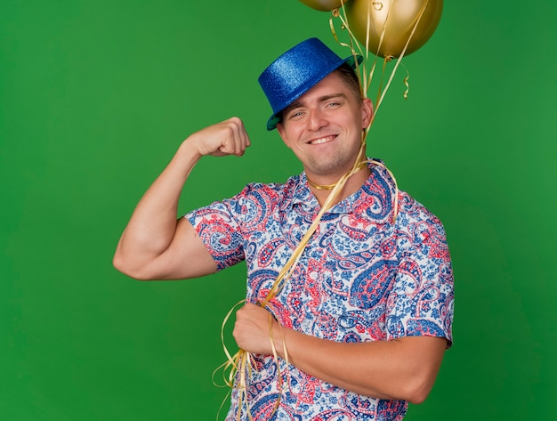 Glimlachende jonge partijkerel die blauwe hoed draagt die ballons houdt die om hals worden gebonden die op groene achtergrond wordt geïsoleerd