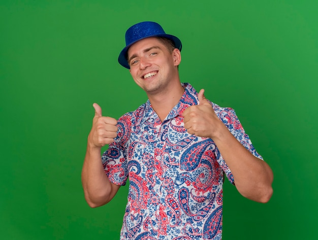 Glimlachende jonge partijkerel die blauwe hoed draagt die duimen toont die omhoog op groen worden geïsoleerd