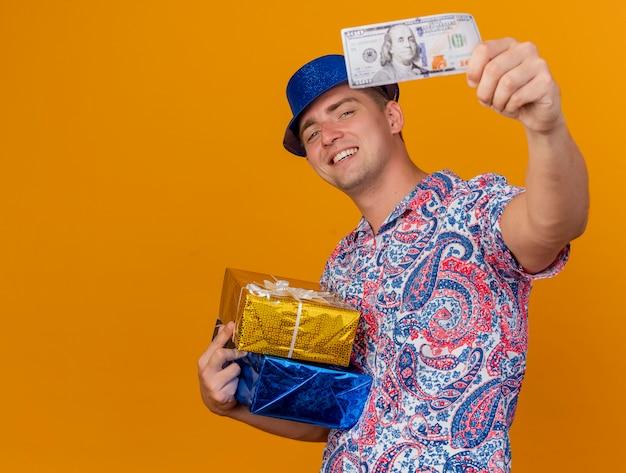 Glimlachende jonge partijkerel die blauwe hoed draagt die giftdozen houdt en contant geld stak bij camera die op oranje achtergrond met exemplaarruimte wordt geïsoleerd