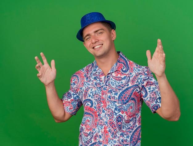 Glimlachende jonge partijkerel die blauwe hoed draagt die handen uitspreidt die op groene achtergrond worden geïsoleerd